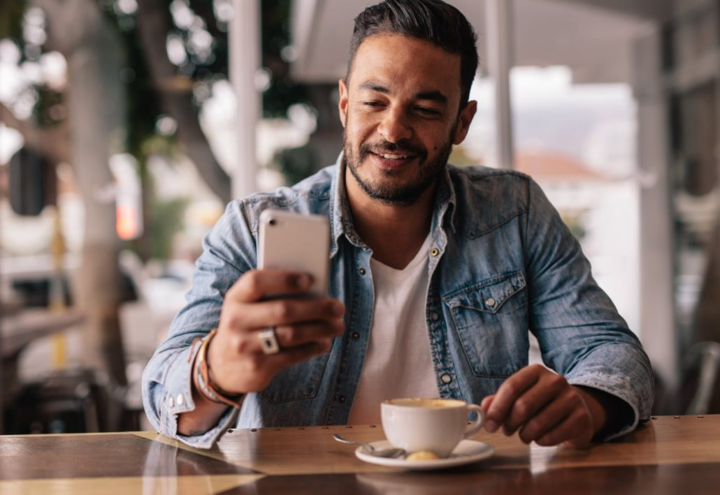 Man receiving a text message promotion during morning coffee